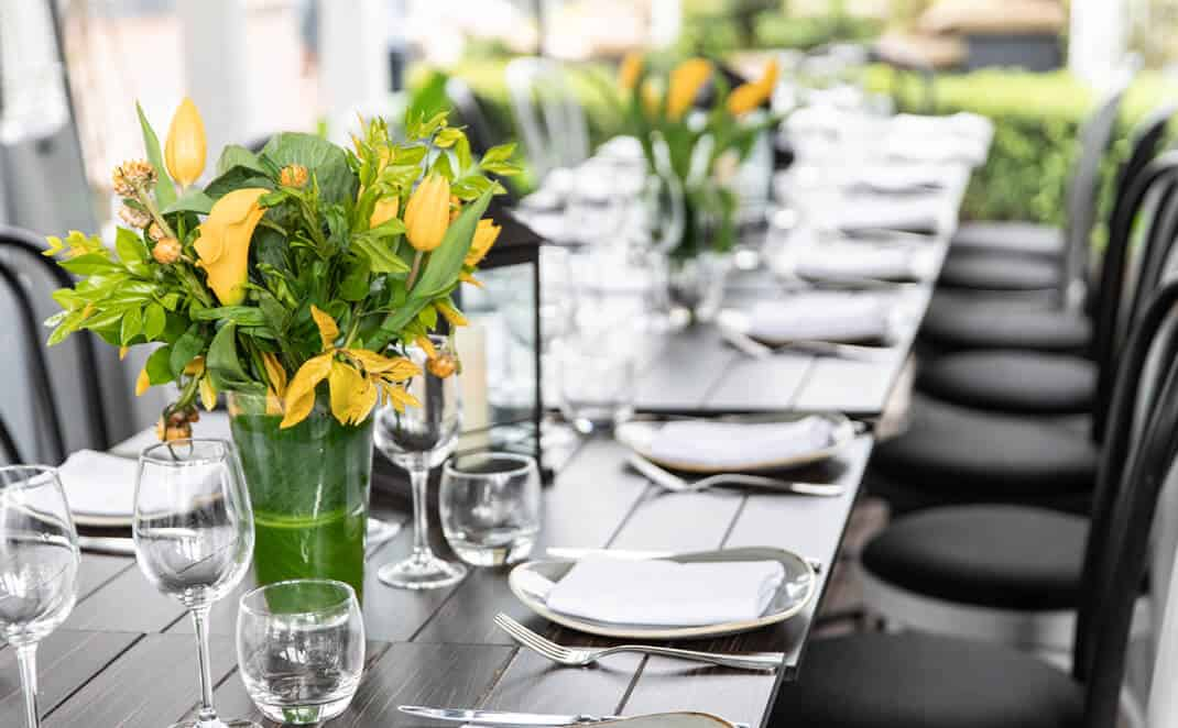 Vases of yellow flowers on dinner table